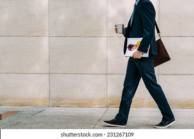 Cropped image of businessman with coffee and magazine going to work