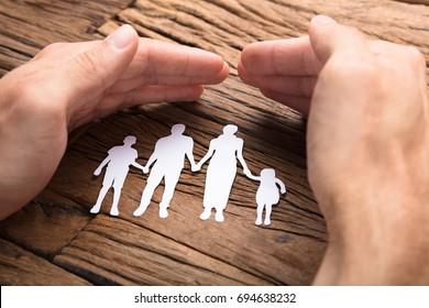 Cropped image of businessman covering paper family at wooden table