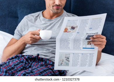 cropped image of businessman with cup of coffee reading business newspaper in bed at home