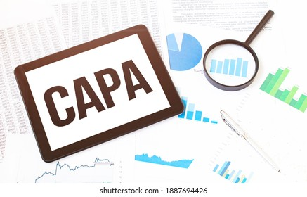 Cropped image of businessman examining graph on digital tablet with magnifying glass at office desk. Text CAPA