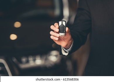 Cropped image of businessman holding a car key while standing in car dealership