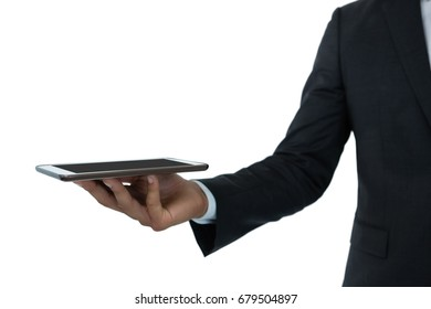 Cropped image of businessman holding digital tablet while standing against white background