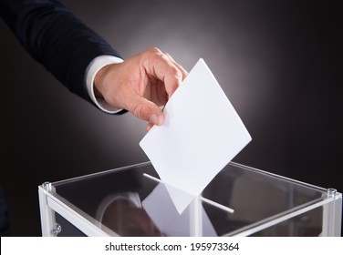 Cropped image of businessman inserting ballot in box on desk against black background