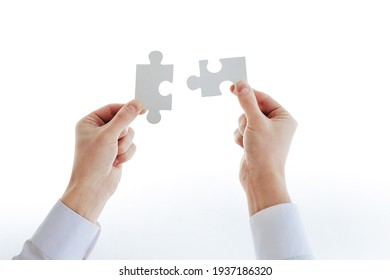 cropped image of a businessman looking at the puzzle pieces.