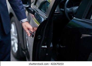 Cropped image of businessman opening door on his car
