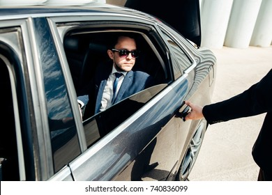 Cropped image of businessman opening door on his car.