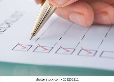 Cropped image of businessman preparing checklist at office desk