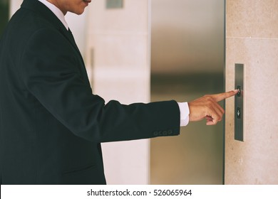 Cropped image of businessman pushing button of elevator