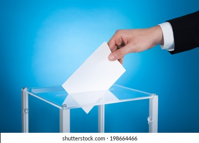 Cropped image of businessman putting paper in election box against blue background