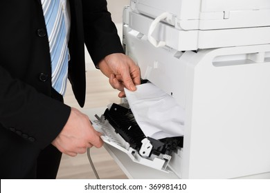 Cropped image of businessman removing paper stuck in printer at office