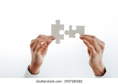 cropped image of a businessman showing puzzle pieces.