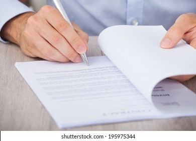 Cropped image of businessman signing contract at desk
