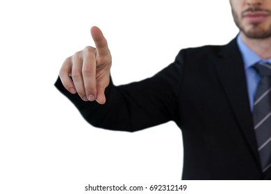 Cropped image of businessman touching index finger on invisible screen against white background