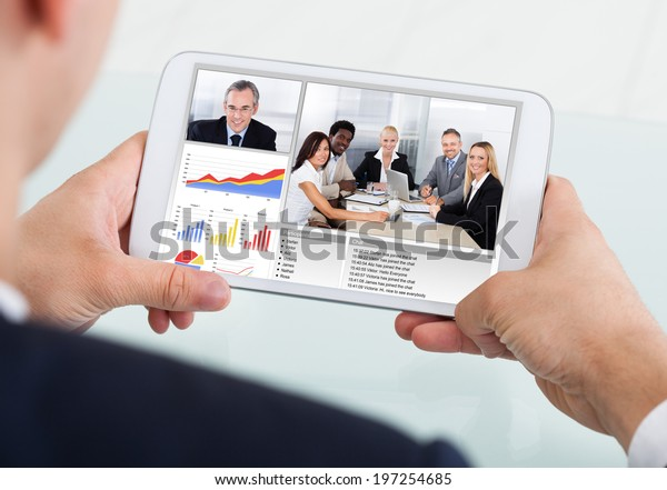 Cropped image of businessman video conferencing with team on digital tablet at desk in office