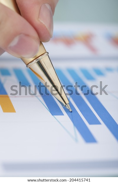Cropped image of businessman's hand showing diagram on financial report with pen