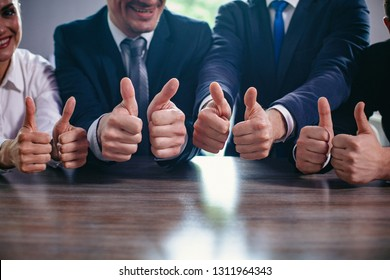 Cropped Image Of Businessmen Holding Their Big Thumbs Up While Sitting In A Row. Selective Focus On Business People s Hands With Big Thumbs Up. Success Concept
