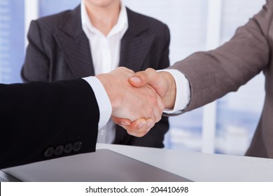 Cropped image of businessmen shaking hands in front of female colleague at office