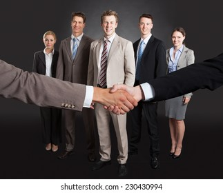 Cropped image of businessmen shaking hands with confident team standing behind over gray background