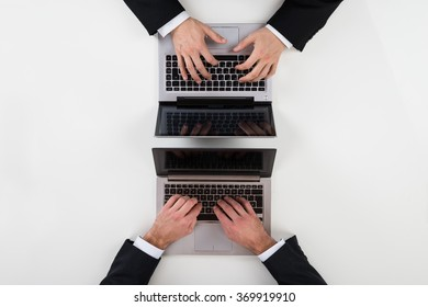 Cropped image of businessmen using laptops at white table in office
