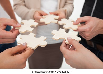 Cropped image of businesspeople joining puzzle pieces in office