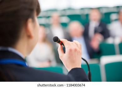 Cropped image of businesswoman giving speech on microphone in lecture room