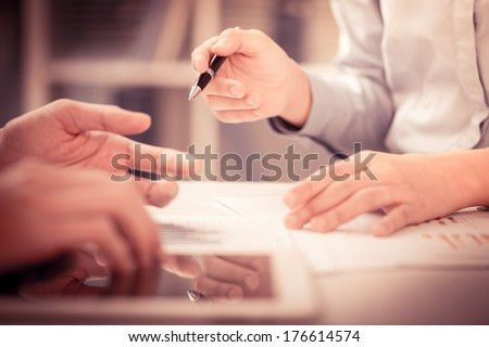 Cropped image of a businesswoman holding a pen and pointing at something while dealing with her colleague on the foreground
