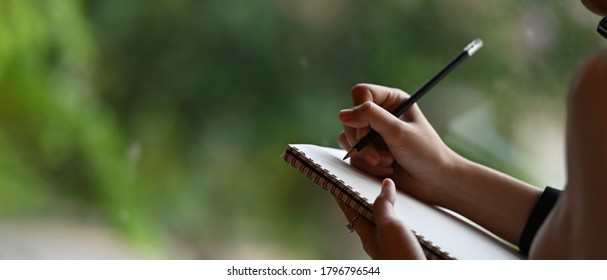 Cropped image of a businesswoman's hand is taking notes while standing over the office glass wall.