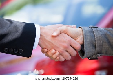 Cropped image of car dealer and female client shaking hands at dealership