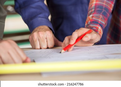 Cropped image of carpenter's hands near blueprint at table in workshop