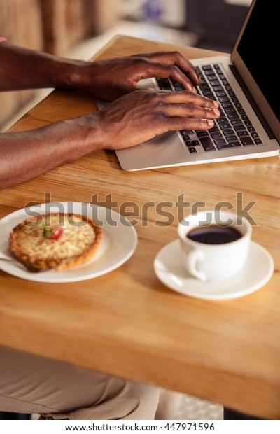 Cropped image of casual man using laptop at coffee shop