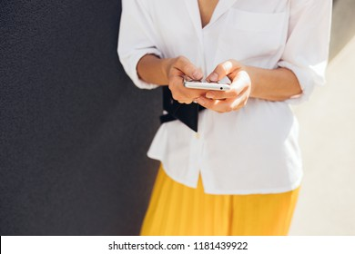 Cropped image of Caucasian young female reading or texting text message on mobile phone on gray wall outdoor in the city. Young woman using free wireless via smart phone on the street. Copy space