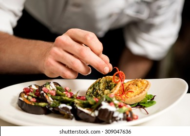 Cropped image of chef garnishing delicious dish