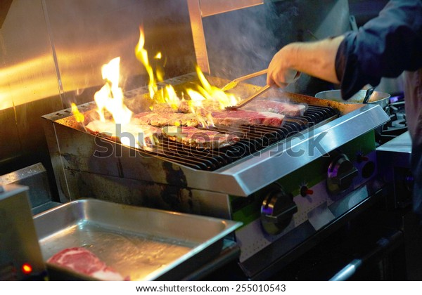 Cropped image of chef grilling steaks in commercial kitchen