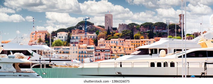 Cropped image cloudy bright sunny sky luxury rich yachts moored at Port Le Vieux view to the Le Suquet old town view of Cannes, France
