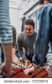 cropped image of colleagues playing in table soccer at modern office