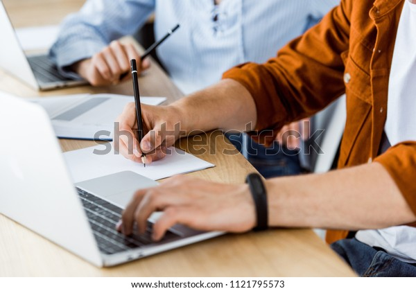 cropped image of colleagues using laptops for working on new startup project in office