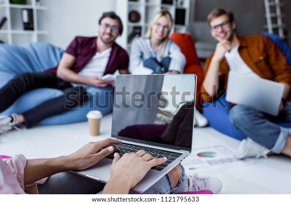 cropped image of colleagues working on startup project in office with laptop