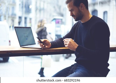 Cropped image of concentrated businessman reading worried sms message on mobile phone sitting at laptop computer with mock up area for your advertising webpage.Pensive male received strange email