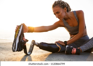 Cropped image of concentrated disabled athlete woman with prosthetic leg doing stretching exercises while sitting at the beach