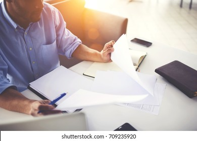 Cropped image of concentrated young businessman checking reports and noting accountancy in blank pages,pensive busy dark skinned male manager pondering on accountings doing paperwork at working place