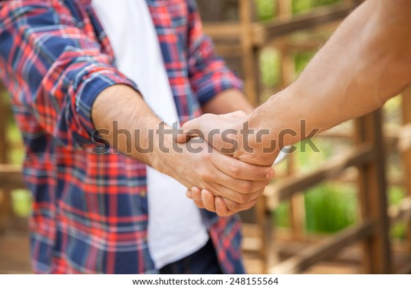 Cropped image of construction workers shaking hands in cabin at site