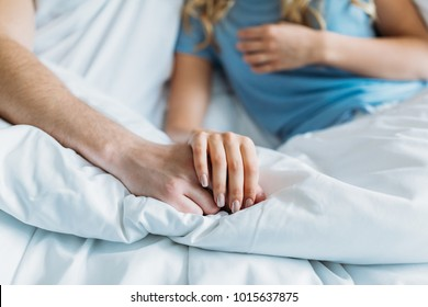 cropped image of couple holding hands in bed