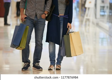 Cropped image of couple with many paper-bags standing in shopping mall