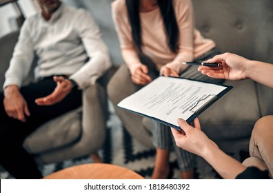 Cropped image of couple signing divorce agreement. Female lawyer giving documents to husband and wife who are going to divorce. Canceling marriage