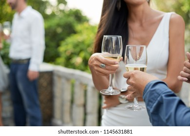 Cropped image of couple talking and drinking sparkling wine at party