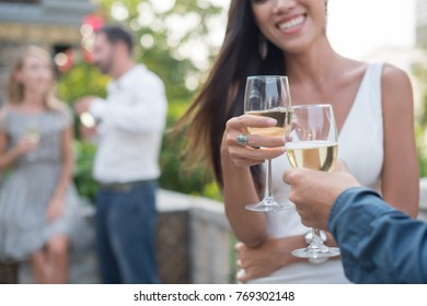 Cropped image of couple toasting at cocktail party