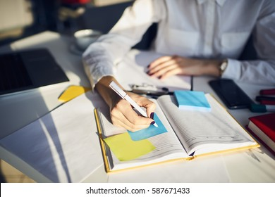 Cropped image of creative female secretary creating planning for executive noting important meeting and events organizing work of busy boss while sitting at working place in coworking office