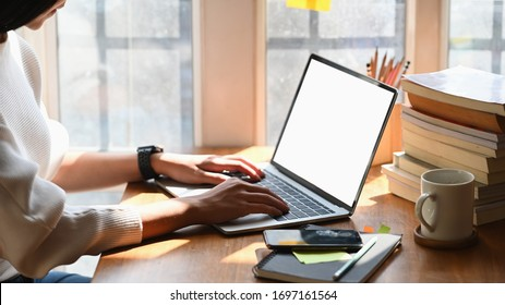 Cropped image of creative woman's hands typing on computer laptop that putting on wooden working desk and surrounded by stack of books, pencil holder, coffee cup and smartphone. Orderly workspace.