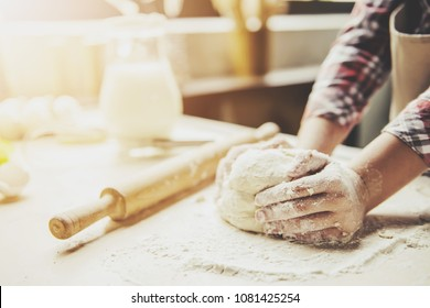 Cropped image of cute little girl kneading the dough for baking