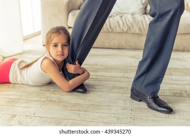 Cropped image of cute little girl looking at camera while hugging her father's leg not letting him go